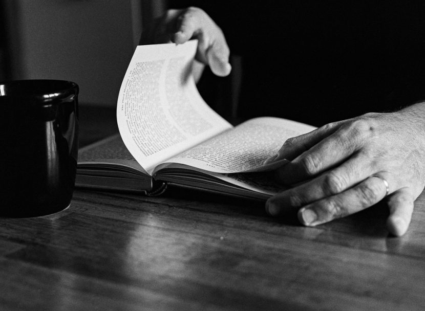 The hands of a man reading book on a table